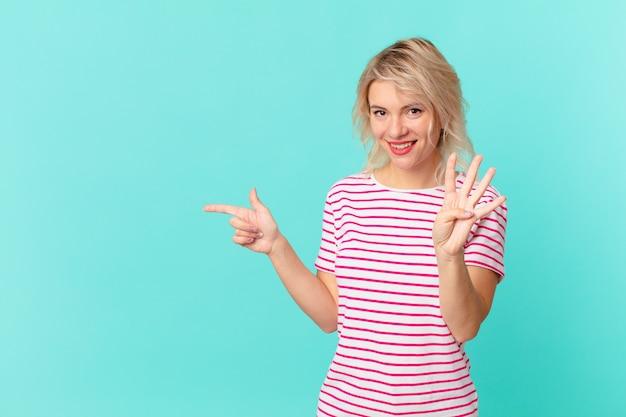 Młoda ładna kobieta uśmiechnięta i wyglądająca przyjaźnie, pokazująca cyfrę cztery