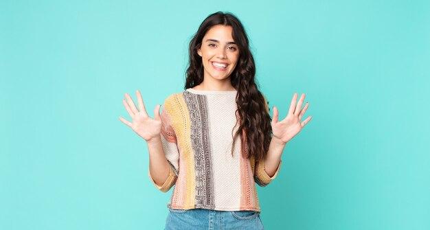 Młoda ładna kobieta uśmiechnięta i wyglądająca przyjaźnie, pokazująca cyfrę dziesięć lub dziesiątą ręką do przodu, odliczając w dół