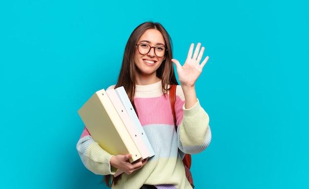 Młoda ładna kobieta uśmiechnięta i wyglądająca przyjaźnie, pokazująca cyfrę piątą lub piątą z ręką do przodu, odliczającą w dół