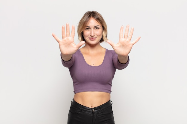 Młoda ładna kobieta uśmiechnięta i wyglądająca przyjaźnie, pokazująca liczbę dziesięć lub dziesiątą ręką do przodu, odliczając w dół