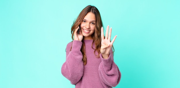 Młoda ładna kobieta uśmiechnięta i wyglądająca przyjaźnie, pokazująca numer cztery i używająca smartfona