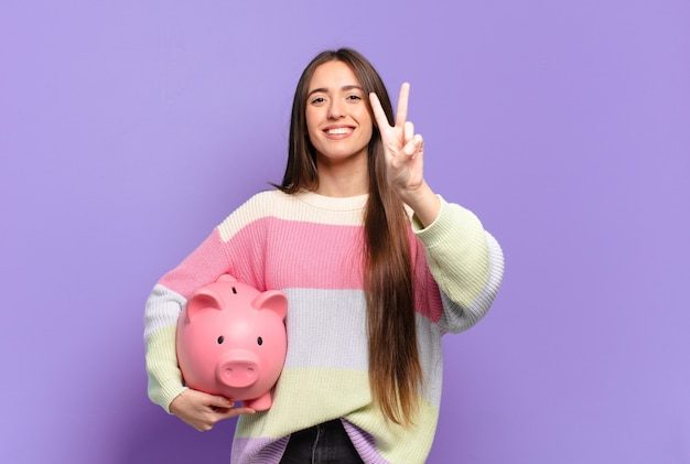 Młoda ładna kobieta uśmiechnięta i wyglądająca przyjaźnie, pokazująca numer dwa lub drugi z ręką do przodu, odliczając w dół