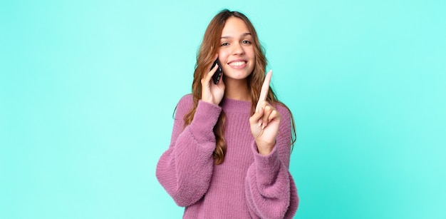 Młoda ładna kobieta uśmiechnięta i wyglądająca przyjaźnie, pokazująca numer jeden i korzystająca ze smartfona