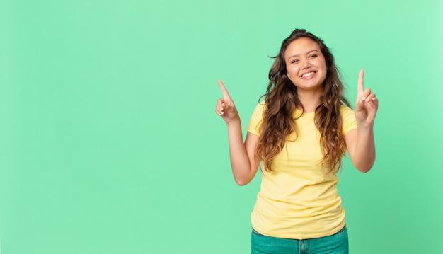 Młoda ładna kobieta uśmiechnięta i wyglądająca przyjaźnie, pokazująca numer jeden i wskazująca miejsce na kopię