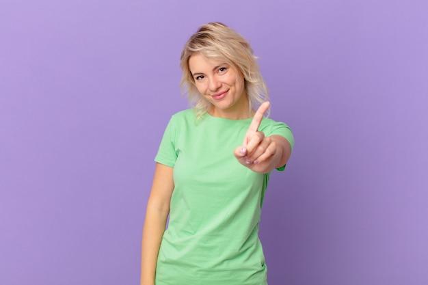 Młoda ładna kobieta uśmiechnięta i wyglądająca przyjaźnie, pokazująca numer jeden