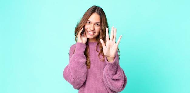 Młoda ładna kobieta uśmiechnięta i wyglądająca przyjaźnie, pokazująca numer pięć i korzystająca ze smartfona