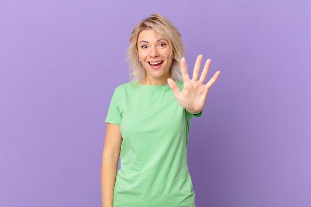 Młoda ładna kobieta uśmiechnięta i wyglądająca przyjaźnie, pokazująca numer pięć