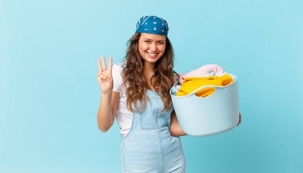 Młoda ładna kobieta uśmiechnięta i wyglądająca przyjaźnie, pokazująca numer trzy i trzymająca kosz na pranie