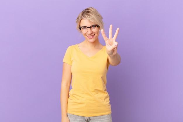 Młoda ładna kobieta uśmiechnięta i wyglądająca przyjaźnie, pokazująca numer trzy