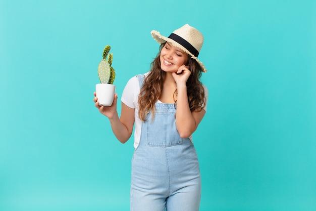 Młoda ładna kobieta uśmiechnięta radośnie i marząca na jawie lub wątpiąca i trzymająca kaktusa