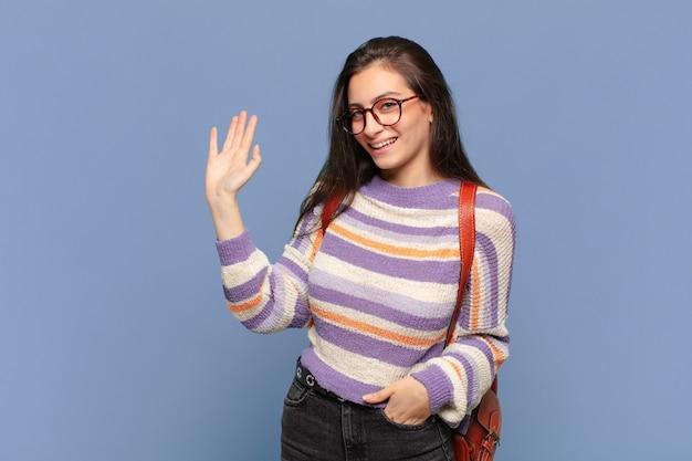 Młoda, ładna kobieta, uśmiechnięta radośnie i radośnie, machająca ręką, witająca cię i pozdrawiająca lub żegnająca się. koncepcja studenta