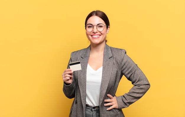 Młoda ładna kobieta uśmiechnięta radośnie z ręką na biodrze i pewną siebie, pozytywną, dumną i przyjazną postawą