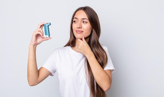 Młoda ładna kobieta uśmiechnięta ze szczęśliwym, pewnym siebie wyrazem twarzy z ręką na brodzie. koncepcja astmy