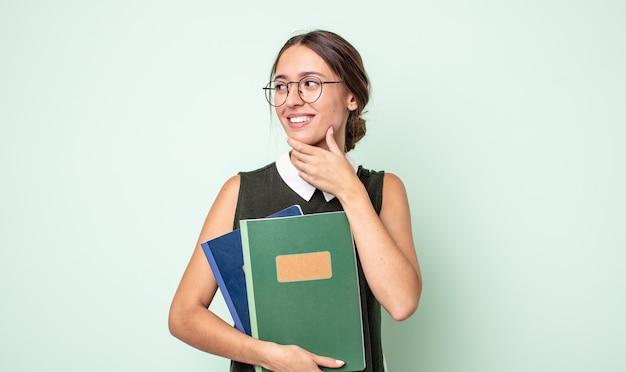 Młoda ładna kobieta uśmiechnięta ze szczęśliwym, pewnym siebie wyrazem twarzy z ręką na brodzie. koncepcja uniwersytecka
