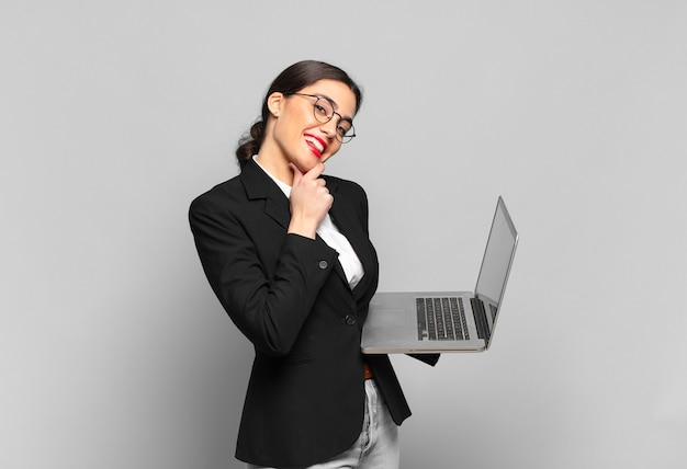 Młoda ładna kobieta uśmiechnięta ze szczęśliwym, pewnym siebie wyrazem twarzy z ręką na brodzie, zastanawiająca się i patrząca w bok. koncepcja laptopa
