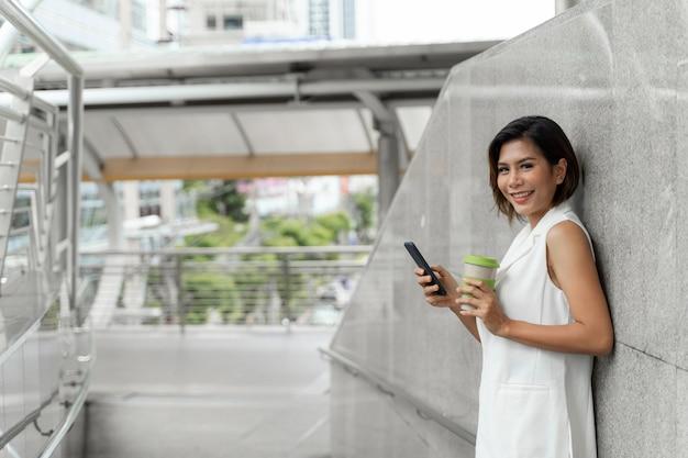 Młoda ładna kobieta używa smartphone publicznie