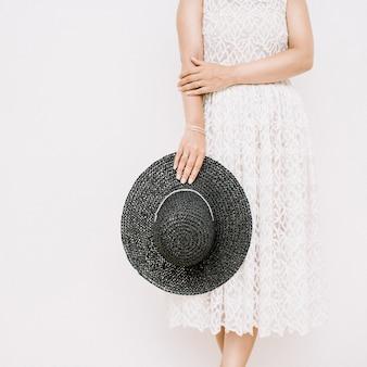 Młoda ładna kobieta w białej sukni z czarnym kapeluszem