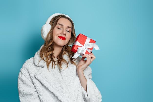 Młoda ładna kobieta w białym płaszczu ze sztucznego futra i futrzanych słuchawkach z czerwoną szminką trzyma pudełko w dłoniach, uśmiecha się, sny na białym tle na niebieskiej ścianie. skopiuj miejsce. prezenty noworoczne 2021