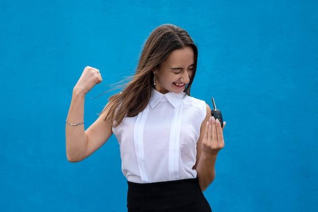 Młoda ładna kobieta w biznesowej tkaninie trzyma kluczyk na niebieskim tle
