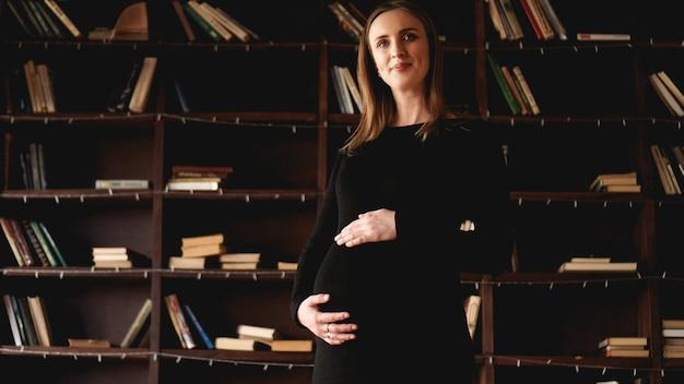 Młoda ładna kobieta w ciąży w czarnej sukience w studio - wnętrze na poddaszu