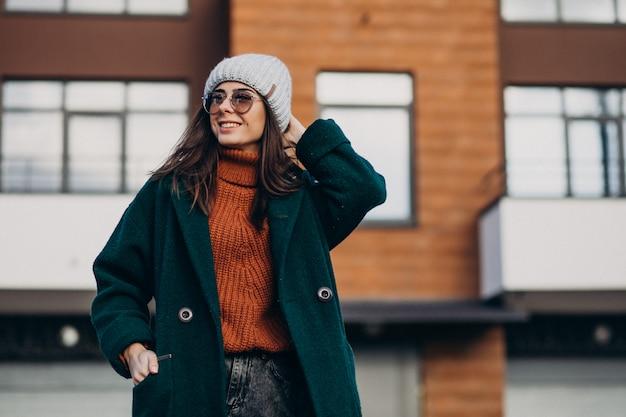 Młoda ładna kobieta w ciepłym płaszczu przy domu