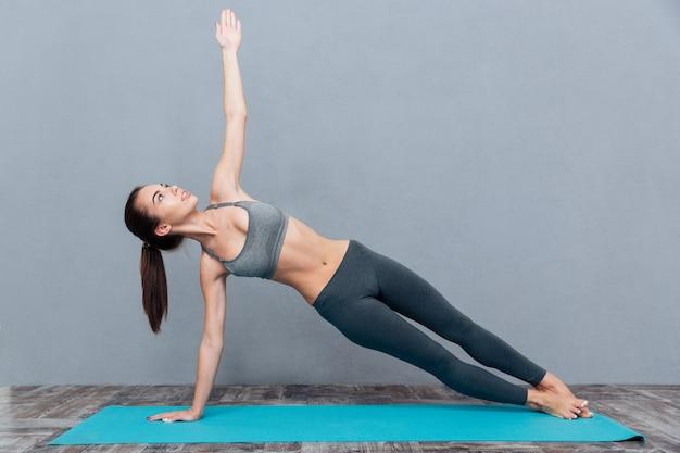 Młoda ładna kobieta w czarnej odzieży sportowej ćwiczy jogę na szarym tle
