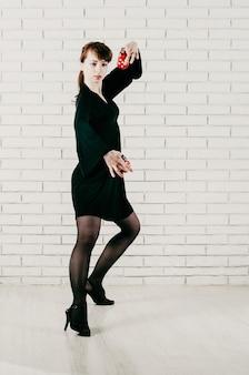Młoda ładna kobieta w czarnej sukience tańczy flamenco z czerwonymi kastanietami białym ceglanym tłem