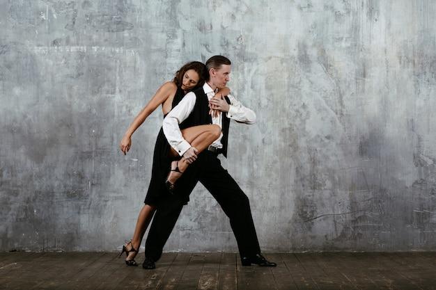 Młoda ładna kobieta w czarnej sukni i mężczyzna tańczy tango
