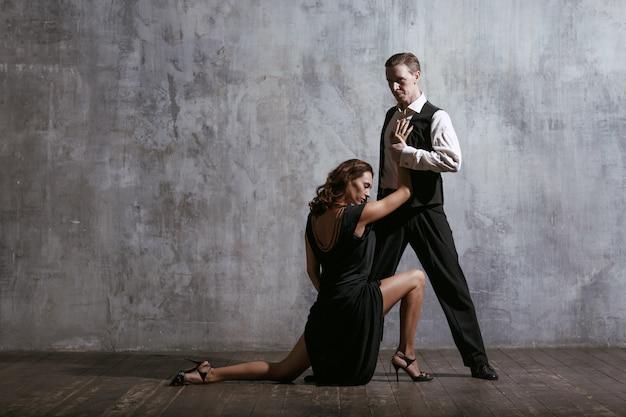 Młoda ładna kobieta w czarnej sukni i tango tańca człowieka
