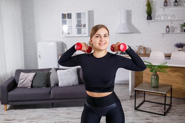 Młoda ładna kobieta w czarnym topie z hantlami w dłoniach uprawiania sportu w domu, fitness w domu podczas kwarantanny. zdrowy tryb życia