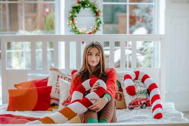 Młoda ładna kobieta w czerwonych bożenarodzeniowych piżamach pozuje z czerwonymi poduszkami siedzi na białym łóżku.