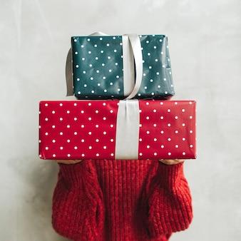 Młoda ładna kobieta w czerwonym swetrze z dzianiny i szarej spódnicy, trzymając duże ręcznie robione pudełka na prezenty
