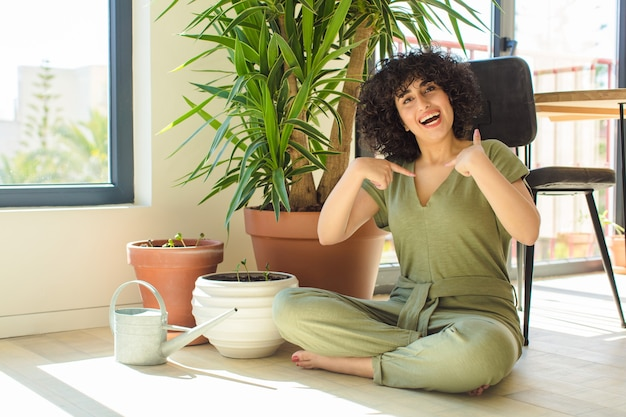 Młoda ładna kobieta w domu, z konewką i roślinami