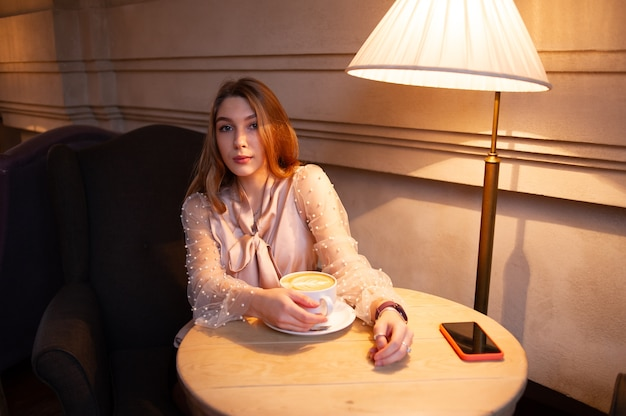 Młoda ładna kobieta w kawiarni. dziewczyna w kawiarni w beżowej bluzce. młoda dziewczyna w kawiarni w czarne szorty i beżową bluzkę z długimi kręconymi włosami. dziewczyna pije kawę w kawiarni. latte, cappuccino