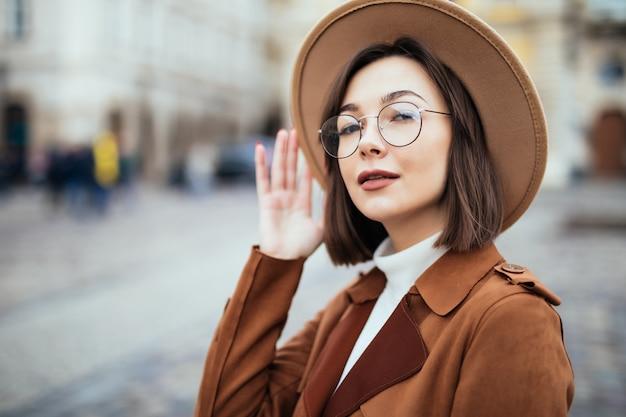 Młoda ładna kobieta w moda kapelusz i brązowy płaszcz pozuje w centrum miasta