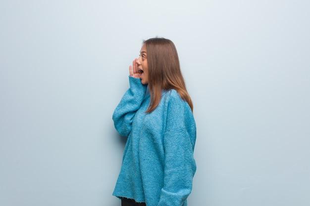 Młoda ładna kobieta w niebieskim swetrze szepcze plotki podtekst