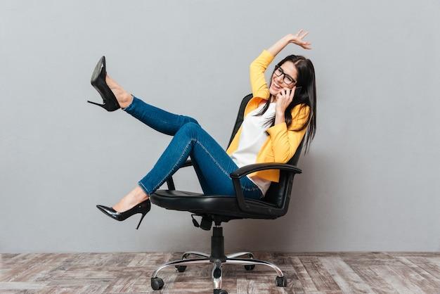 Młoda ładna kobieta w okularach i ubrana w żółtą kurtkę, siedząc na krześle biurowym podczas rozmowy przez telefon na szarej powierzchni.