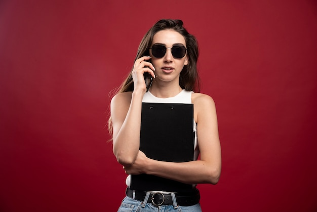 Młoda ładna kobieta w okularach, mówiąc na telefon i trzymając notebooki