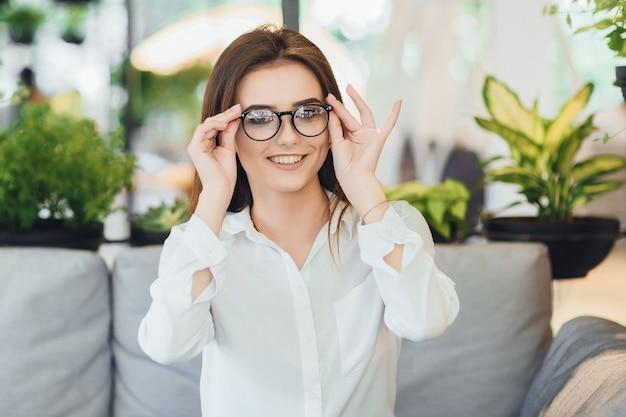 Młoda ładna kobieta w okularach w białej koszuli siedzi w biurze
