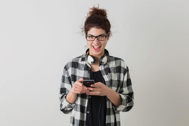 Młoda ładna kobieta w okularach, za pomocą smartfona, emocjonalny, śmiejący się, pozytywny, szczęśliwy, słuchawki, na białym tle, koszula w kratkę, student, wpisywanie wiadomości