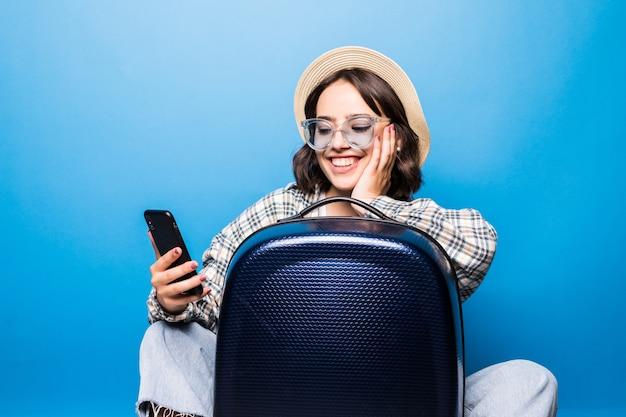 Młoda ładna kobieta w okulary i słomkowy kapelusz z walizką patrzy do telefonu na białym tle. podróżowanie samolotem.