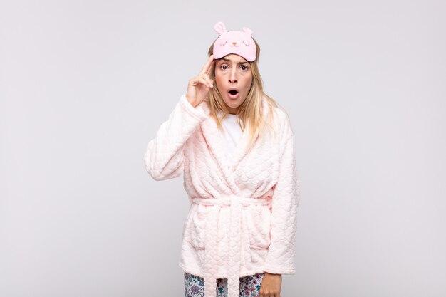 Młoda ładna kobieta w piżamie, wyglądająca na zaskoczoną, z otwartymi ustami, zszokowana, zdająca sobie sprawę z nowej myśli, pomysłu lub koncepcji