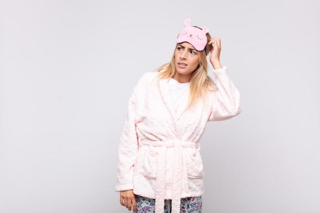 Młoda ładna kobieta w piżamie, zdziwiona i zdezorientowana, drapiąca się po głowie i spoglądająca w bok