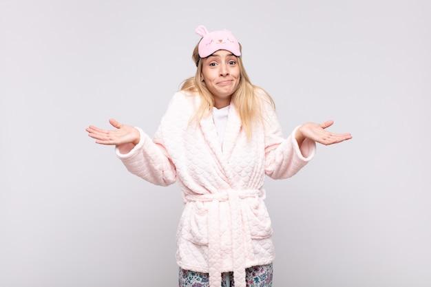 Młoda ładna kobieta w piżamie, zdziwiona i zdezorientowana, wątpiąca, ważąca lub wybierając różne opcje z zabawnym wyrazem twarzy