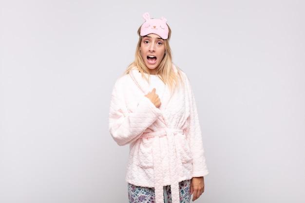 Młoda ładna kobieta w piżamie, zszokowana i zaskoczona, z szeroko otwartymi ustami, wskazująca na siebie