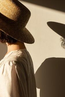 Młoda ładna kobieta w słomkowym kapeluszu i białej sukience sukienki. sylwetka w słońcu