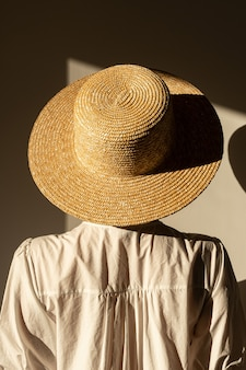 Młoda ładna kobieta w słomkowym kapeluszu i białej sukience sukienki