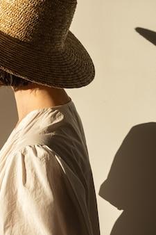 Młoda ładna kobieta w słomkowym kapeluszu i sukience białej sukienki na ścianie. cień słońca na ścianie