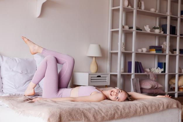 Młoda ładna kobieta w sporcie nosi w domu na łóżku, bawiąc się zabawnie i radośnie
