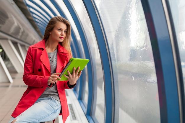 Młoda ładna kobieta w strój dorywczo trzymając tablet laptop w miejskim budynku